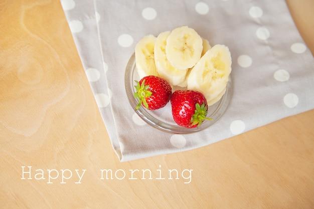 Aardbei en banaan op een glasplaat op een houten achtergrond, die gelukkige ochtend van letters voorzien.