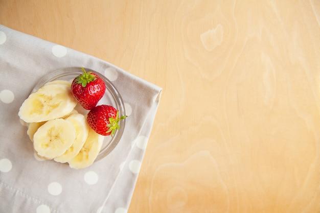 Aardbei en banaan op een glasplaat op een houten achtergrond.