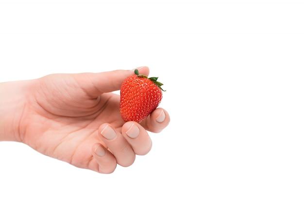 Aardbei in vrouwelijke hand die op een witte achtergrond wordt geïsoleerd