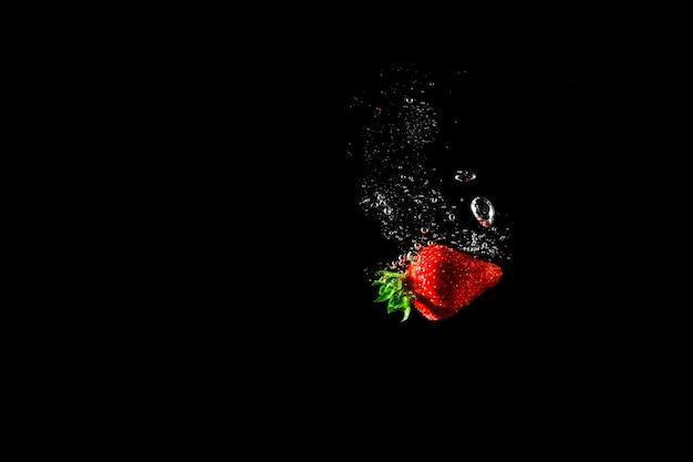 Aardbei in water met zwart.
