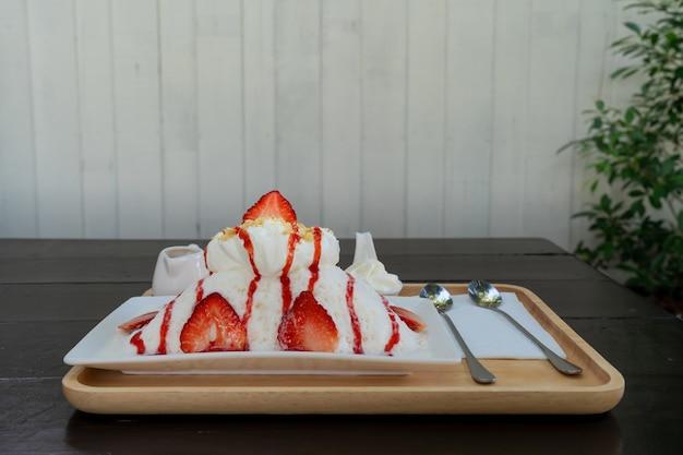 Aardbei kakigori (japanse geschoren ijs dessert melk smaak) of bingsu (korea dessert) serveren op witte plaat met aardbeiensaus en toppings op tafel, zoet eten