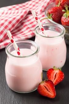 Aardbei milkshake in de glazen pot met rietje op zwarte leisteen oppervlak.