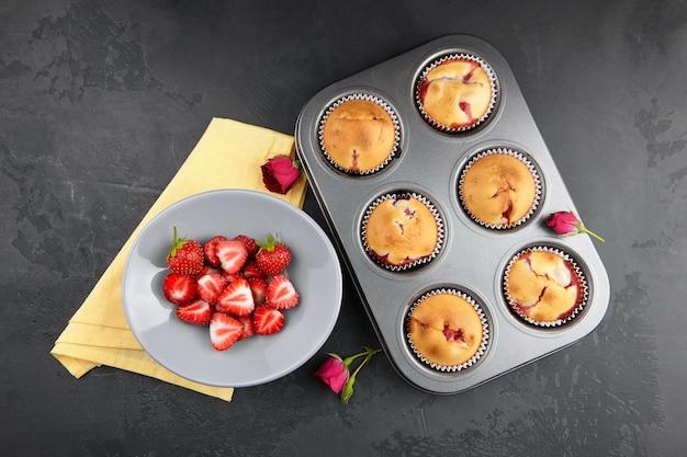 Aardbei muffins met verse bessen op zwarte betonnen achtergrond, plat leggen