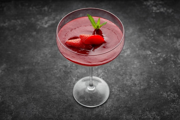 Aardbei panna cotta in een cocktailglas op een donkere tafel