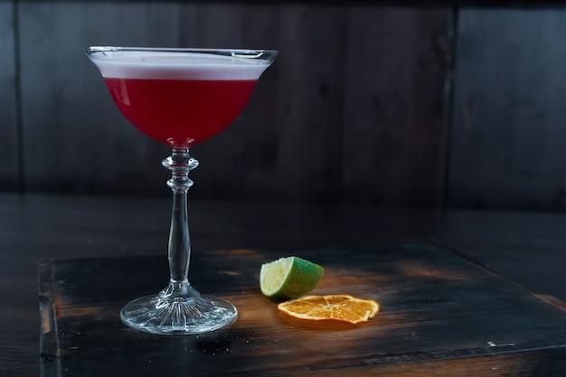 Aardbei tweelaagse heerlijke cocktail met tonic en wodka met bessenlikeur met schuim in een kristalglas staat op een houten bord op een vintage tafel in een restaurant. weekend in een nachtclub.