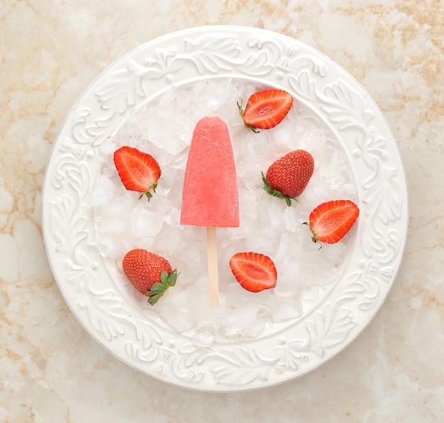 Aardbei yoghurtijs ijslollys met aardbei over ijsblokjes.