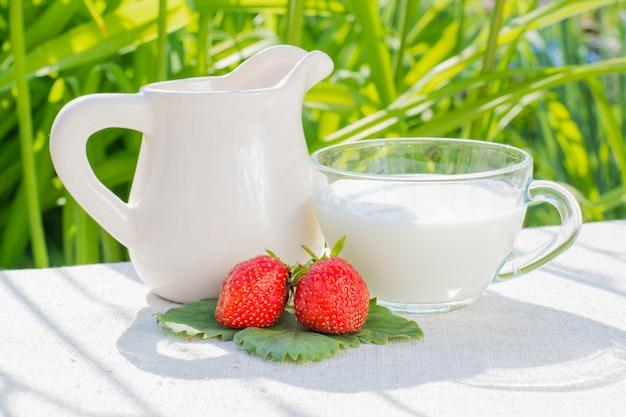 Aardbeibessen en bladeren, een kruik en een kop met melk op een servet op een achtergrond van gras