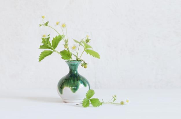 Aardbeibloemen in vaas op witte houten lijst