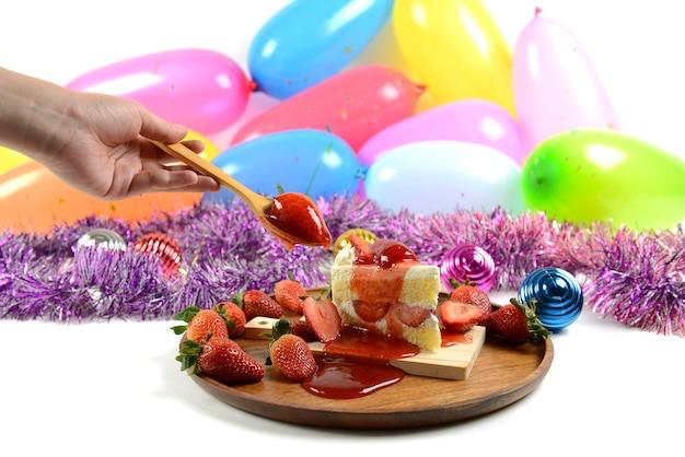 Aardbeicake op de achtergrond van partijballons voor vieringen in specialsdagen.