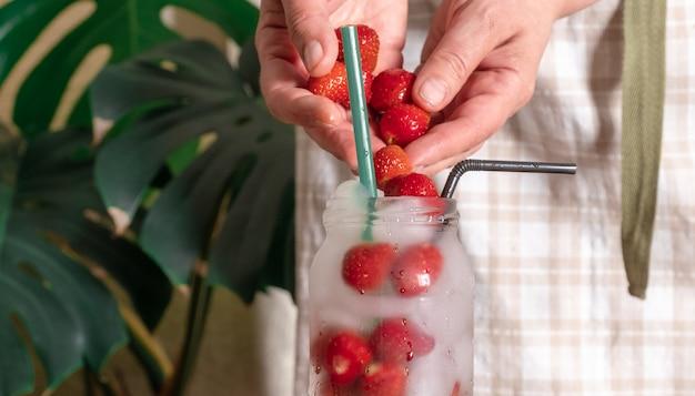Aardbeidrank glas hand witte achtergrond cocktail ijs tropische bladeren