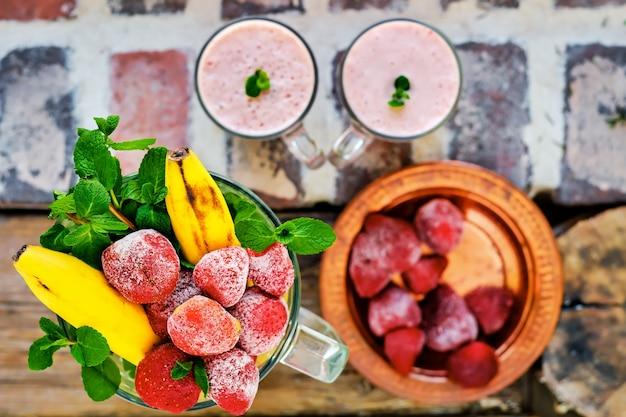 Aardbeien, bananen, muntblaadjes in een mengkom zijn ingrediënten voor het maken van een milkshake. plat leggen, selectieve focus op ingrediënten. gezond eten of snack bovenaanzicht