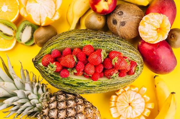 Aardbeien binnen de groene gesaldeerde meloen met kokosnoot; kiwi; mango; banaan; ananas en sinaasappelen op gele achtergrond