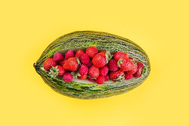 Aardbeien binnen de groene gesaldeerde meloen op gele achtergrond