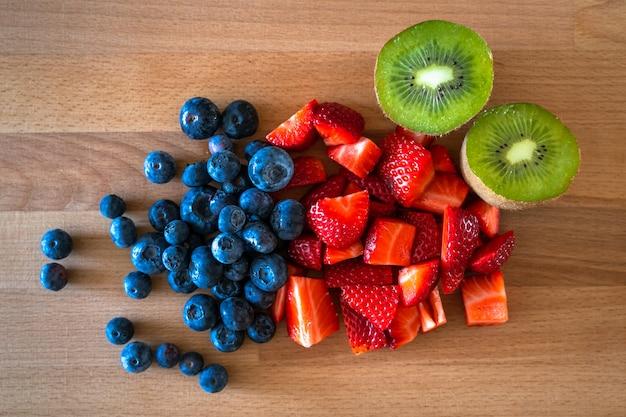 Aardbeien, bosbessen en kiwi's in een houten tafel