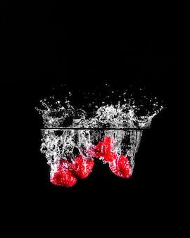 Aardbeien die in het water duiken