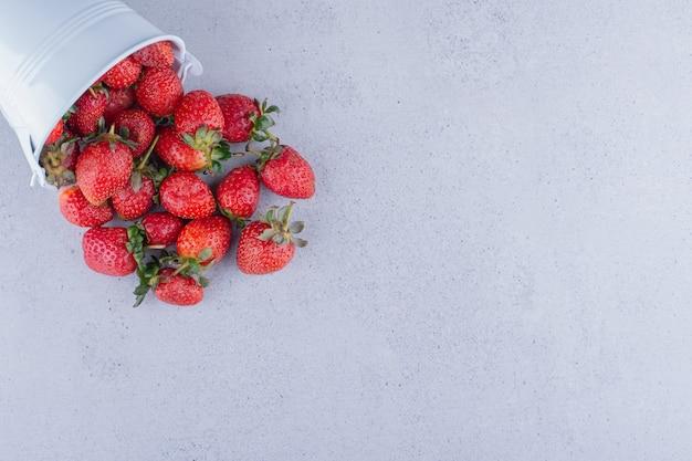 Aardbeien die uit een kleine emmer op marmeren achtergrond morsen. hoge kwaliteit foto