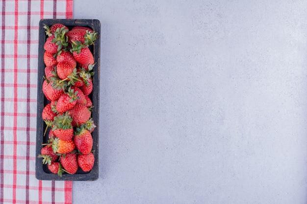 Aardbeien dienblad opgesteld aan de rand van het tafelkleed op marmeren achtergrond. hoge kwaliteit foto