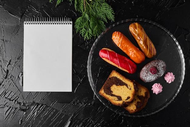 Aardbeien-eclair met chocolademuffin en een receptenboek.