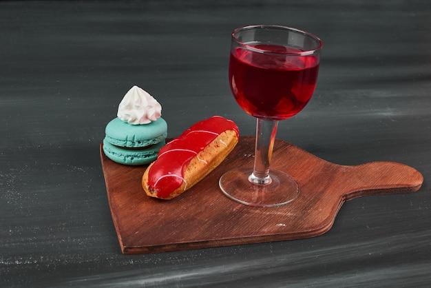 Aardbeien-eclair met franse macarons en een glas wijn.