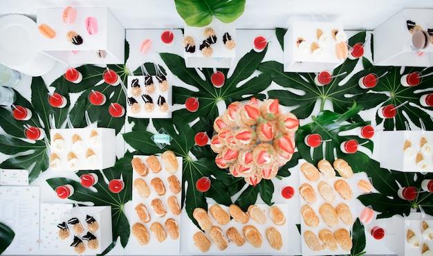 Aardbeien eclairs geserveerd op transparante schotel staan op een tafel met andere snoepjes