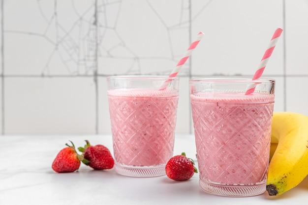Aardbeien- en bananensmoothie of milkshake in glazen met vers fruit en bessen op een witte ondergrond