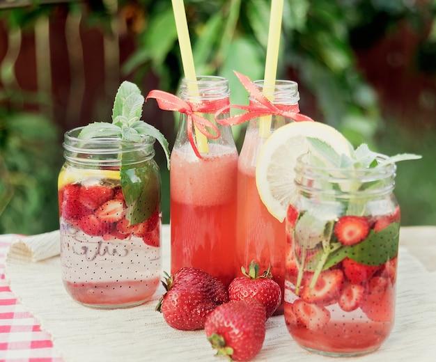 Aardbeien en mint toegediend detoxwater. aardbeienlimonade met ijs en munt als verfrissende zomerdrank in potten. koude frisdranken met fruit.