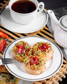 Aardbeien en room gevulde mini bladerdeeg gegarneerd met pistachenoten