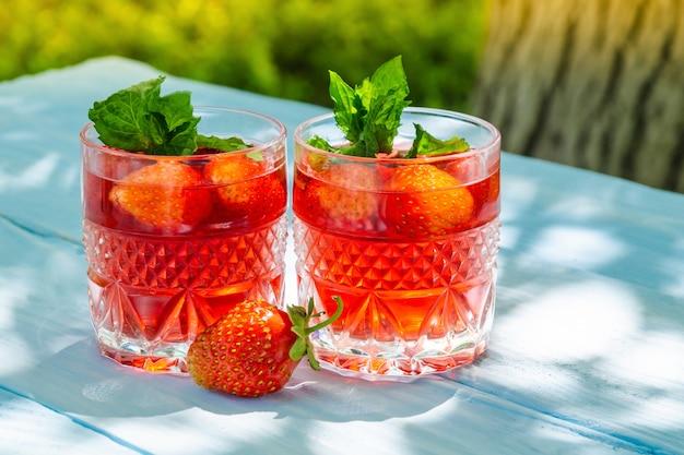Aardbeien en verse dranken met munt op zonnige dag