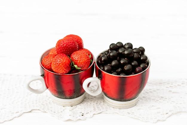 Aardbeien en zwarte bessen in een mok, concept zomer in het dorp.