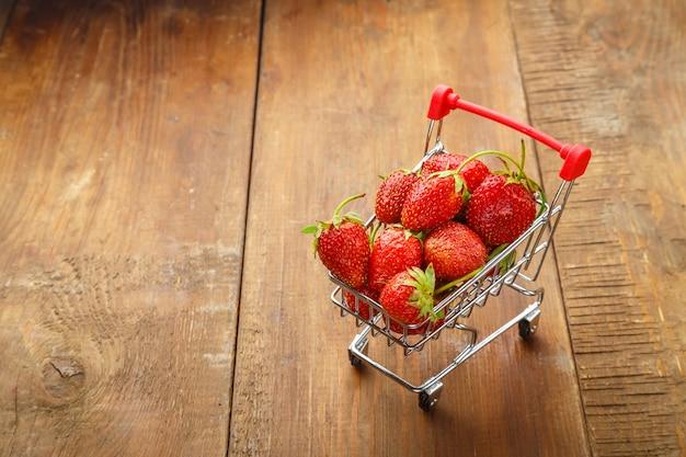 Aardbeien in een boodschappenwagentje op een houten ondergrond.
