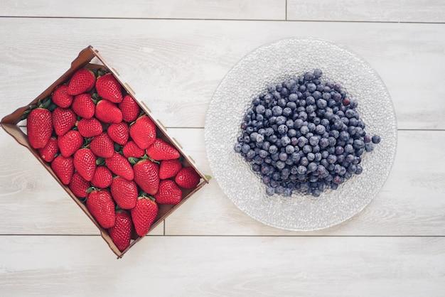 Aardbeien in een doos en bosbessen op een bord