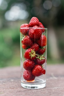 Aardbeien in een glas in de tuin op een houten tafel