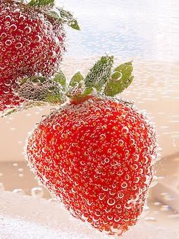 Aardbeien in een glazen container met bubbels in neon toning met verloop