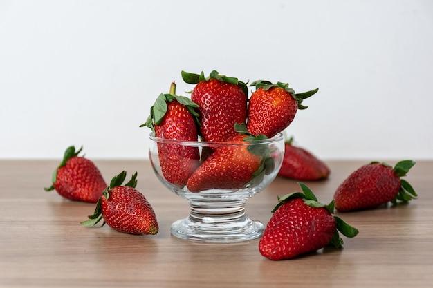 Aardbeien in een glazen pot en verspreid over de houten tafel.