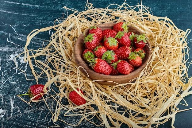 Aardbeien in een houten beker in het nest.