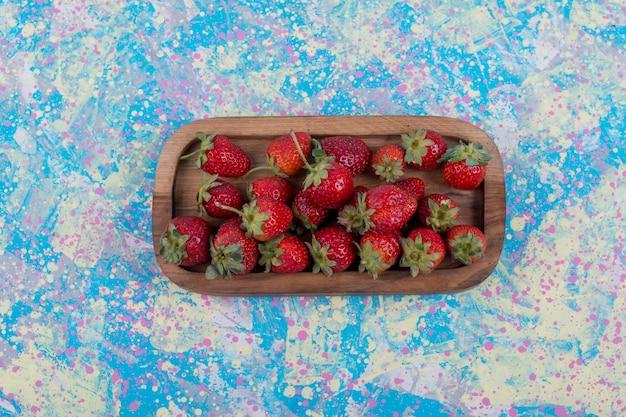 Aardbeien in een houten schotel in het midden