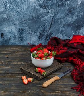Aardbeien in een kom, mes en rode sjaal