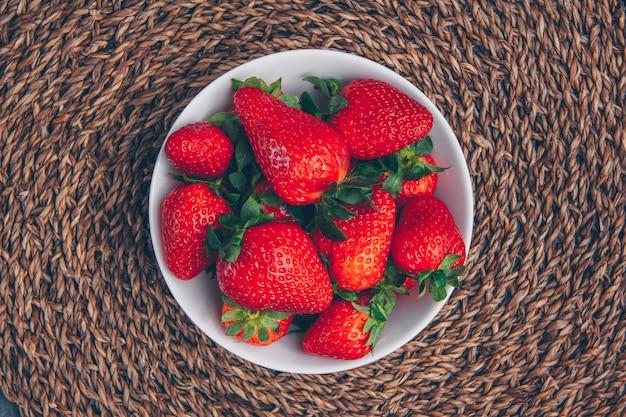 Aardbeien in een kom op een gestructureerde achtergrond. bovenaanzicht.