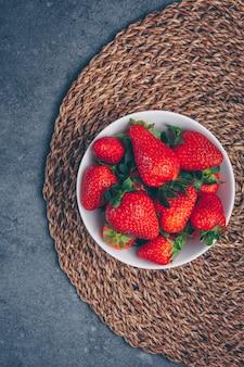 Aardbeien in een kom op een onderzetter en een grijze gestructureerde achtergrond. bovenaanzicht.