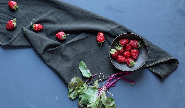 Aardbeien in kom en bladeren op een zwarte mat.