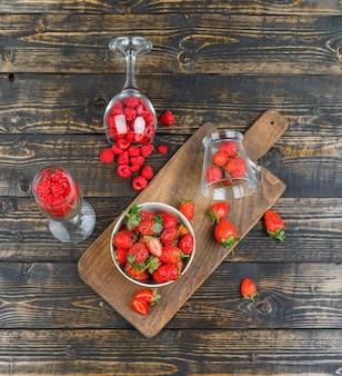 Aardbeien in kom met frambozen in glazen