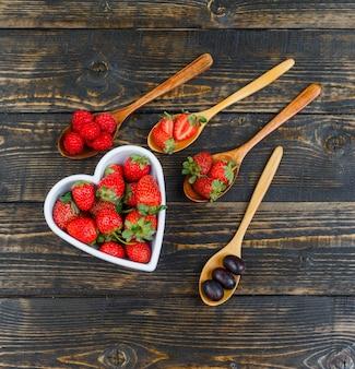 Aardbeien in kom met fruit op houten lepel