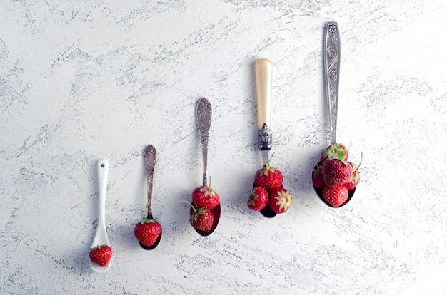 Aardbeien in lepels van verschillende grootte. zomer en gezond eten concept