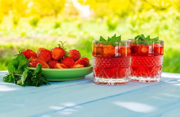 Aardbeien in plaat op tafel en verse drankjes met munt op een zonnige dag