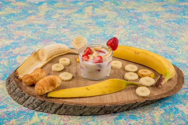Aardbeien in room geserveerd met banaan en bladerdeeg