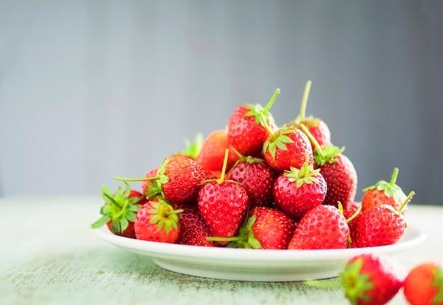 Aardbeien in witte plaat over grijze gradient achtergrond