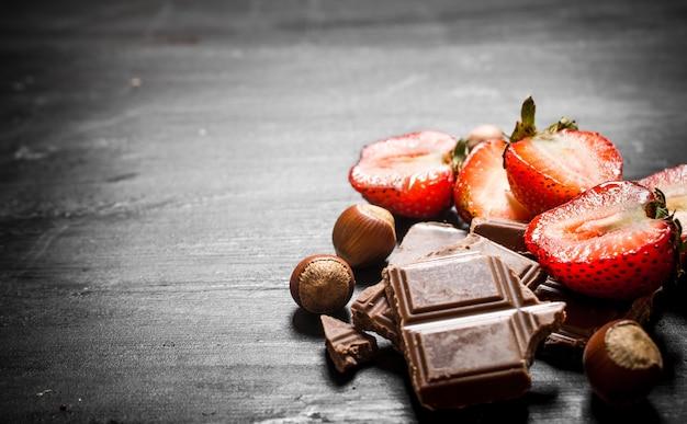Aardbeien met plakjes chocolade en noten. op de zwarte houten tafel.