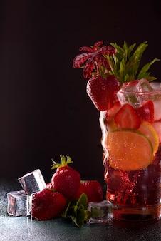 Aardbeien mojito cocktail aan de bar. mojitococktail op zwarte achtergrond. cocktail mojito in de nachtclub