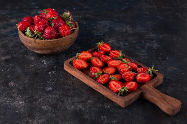 Aardbeien op een houten bord en in een bord
