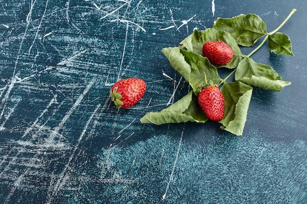 Aardbeien op groene bladeren.